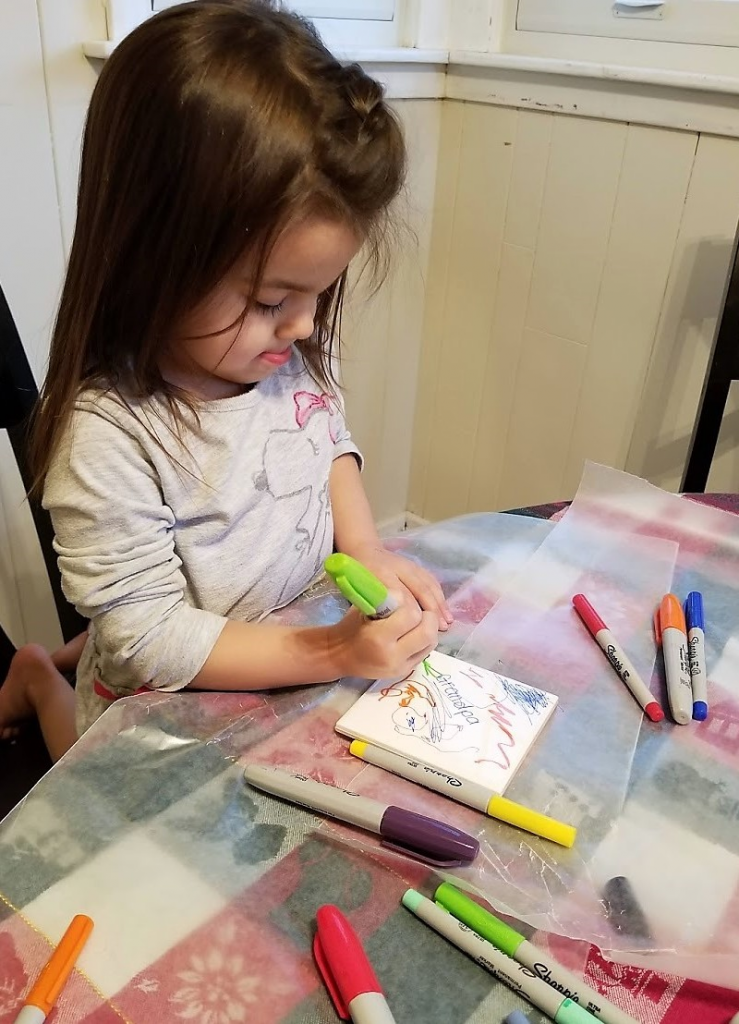 toddler coloring with sharpie on tile